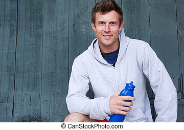 portrait of a young athlete holding water bottle - portrait...
