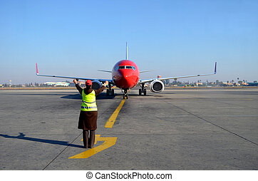 Woman signalling plane at airport - Plane being signalled by...