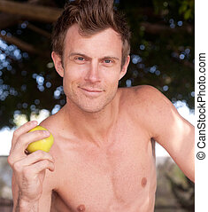 portrait of a young healthy man holding apple