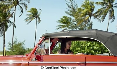 female friends driving, pushing car - two beautiful young...