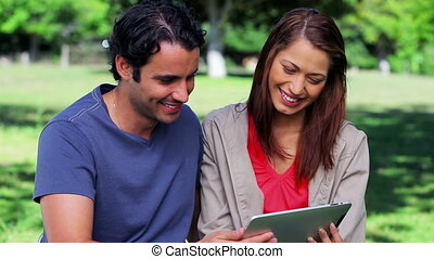 Smiling couple looking at a tablet pc in a parkland