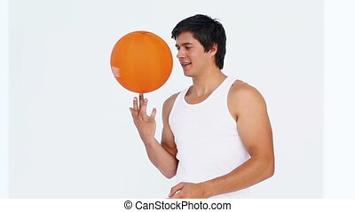 Man spins a basketball on his figer