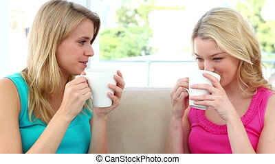 Two blonde women drinking coffee while sitting on a sofa