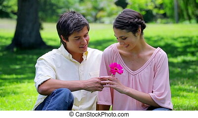 Smiling man giving a pink flower to his girlfriend
