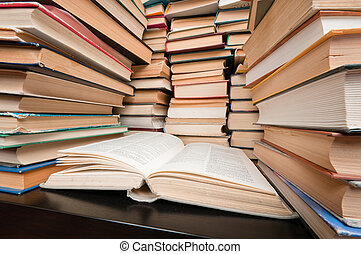 Stacks of books on black table - Big stacks of hardcovered...