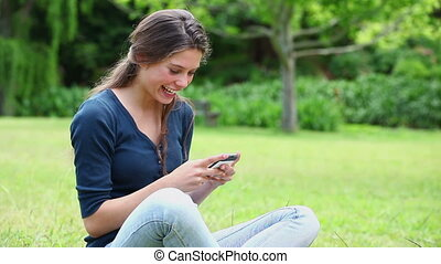 Smiling young woman sending a text in a park