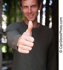 young man giving a thumbs up hand gesture, standing outside