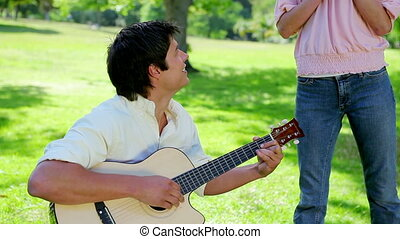 Smiling man playing music with his guitar for his girlfriend...