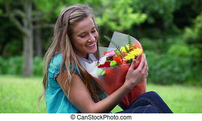 Cheerful woman holding a bunch of flowers in a park