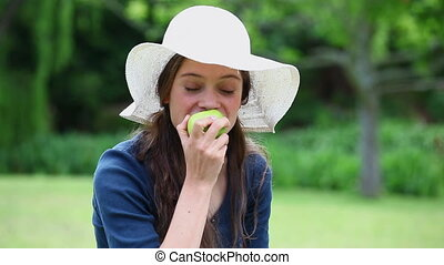 Cheerful woman eating a green apple