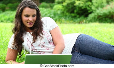 Smiling brunette typing on a beautiful laptop