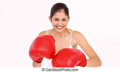 Laughing woman trying to box against white background