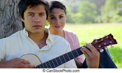 Smiling woman listening to her boyfriend who is playing the guitar