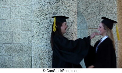 Females graduates embracing each other to congrats