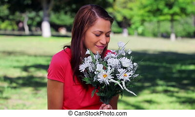 Happy woman laughing while holding flowers in a parkland