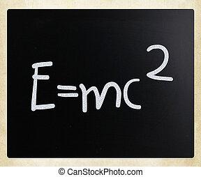 E=mc2 handwritten with white chalk on a blackboard