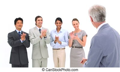 Business team applauding its boss against a white background