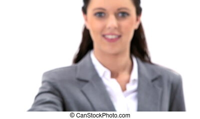 Brunette woman holding a business card against a white...