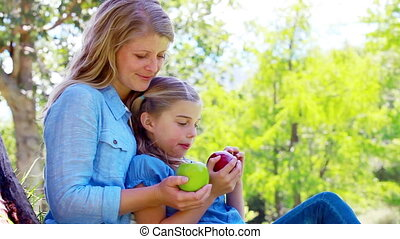 Daughter and mother holding apples