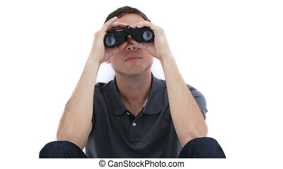 A sitting man is looking through binoculars against a white...