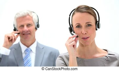 Business people speaking into a headset against a white...