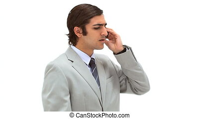 Businessman using his mobile phone against a white...