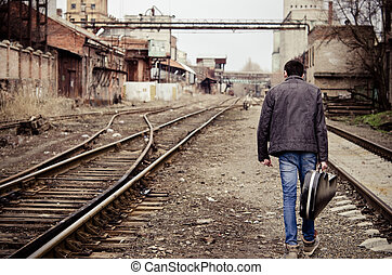 Young man with guitar case is going away among industrial...
