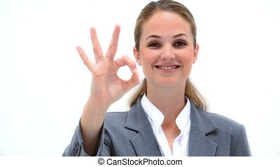 Smiling woman showing the OK sign against a white background