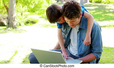 Son and father using a laptop