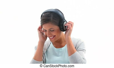 Smiling woman listening to music against a white background