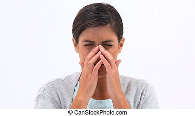 Brunette woman is sneezing against white background