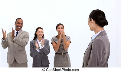 Young woman being congratulated by co-workers against a...