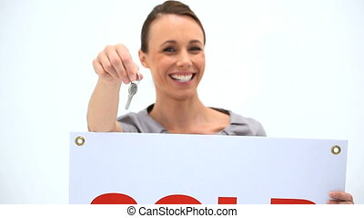 Smiling woman dangling keys against a white background