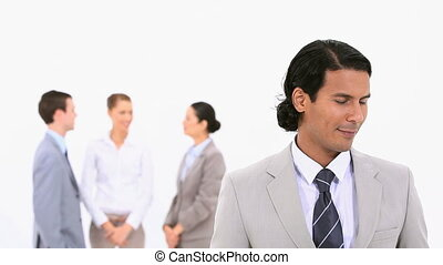 Smiling businessman with colleagues standing behind him
