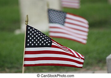 Remembrance Day - A US Flag shot close up in a cemetery with...