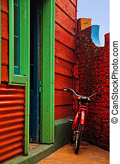Red Bicycle next to a Red Wall - A red bicycle resting...