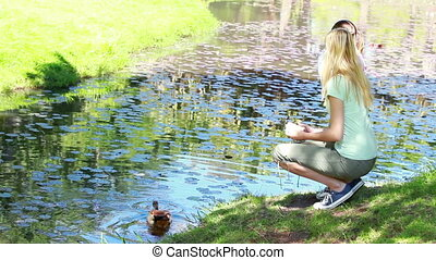 Woman nourishing a duck in a park