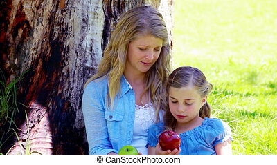 Mother and daughter holding apples
