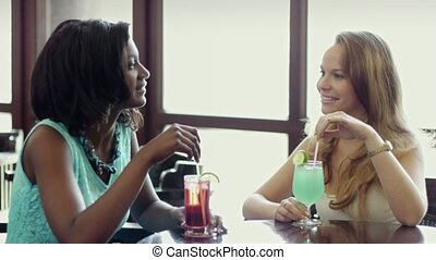 two women having fun in pub - african and latin american...