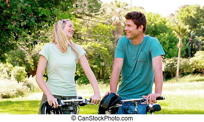 Laughing couple holding bikes in a park