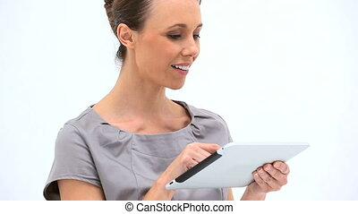 Smiling woman using a tablet computer against a white...