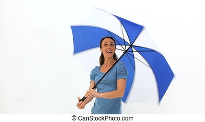 Woman turning her umbrella against white background