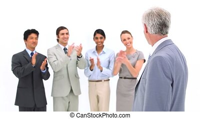 Boss being congratulated by co-workers against a white...