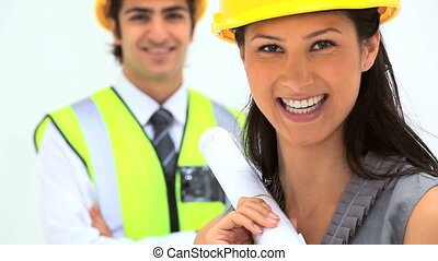 Two business people with safety helmet against white...