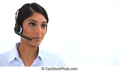 Businesswoman speaking into headset against a white...