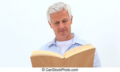 Smiling man reading a novel against a white background