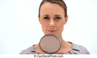 Curious woman using a magnifying glass against a white...