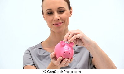 Businesswoman putting money into a piggy bank against white...