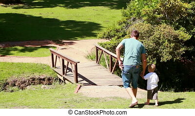 Man walking with his little boy in a park