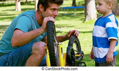 Man playing with a bike wheel with his son in a park